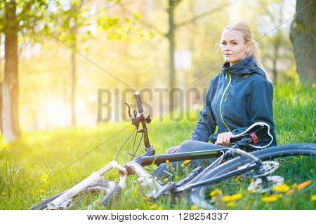 Young woman with bike in spring city at sunset