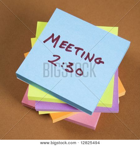 Stack of sticky notes with a meeting reminder.