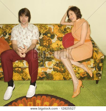 Pretty Caucasian mid-adult woman flirting with shy Caucasian mid-adult man sitting on colorful retro sofa.