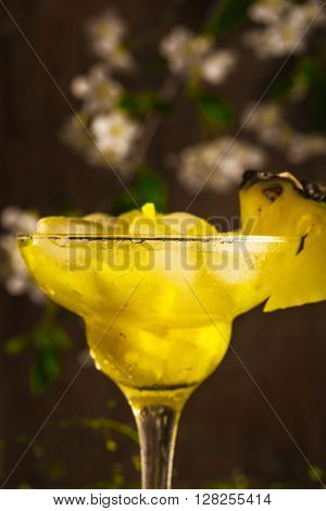 pineapple fruit soft drink with ice on a wooden background with flowers.