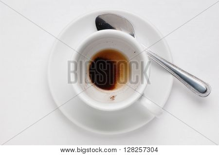 Drunk cup of strong coffee with coffee spent grounds on saucer with spoon against white background, top view with place for text