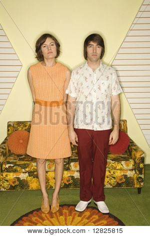 Caucasian mid-adult couple wearing retro clothes standing stiffly in room decorated with vintage furniture.