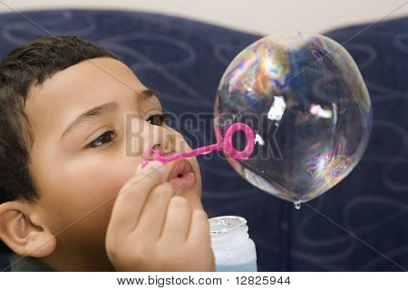 Hispanic boy blowing large soap bubble.
