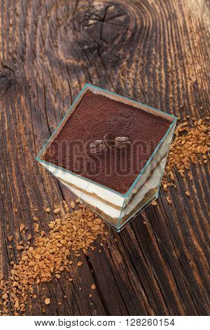 Tiramisu dessert with coffee beans and instant coffee on wooden textured table. Traditional tiramisu dessert rustic country style.