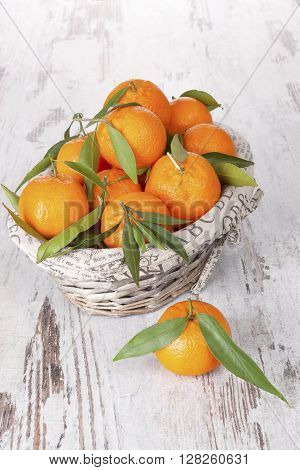 Mandarine fruit in white wooden basket on white wooden table. Provence style.