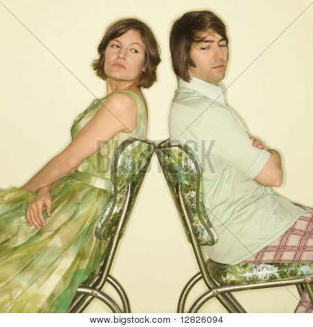 Caucasian mid-adult couple wearing vintage clothing sitting back to back in green vinyl chairs with arms crossed looking angry.