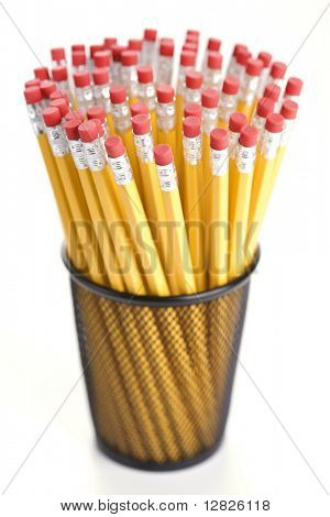 Group of pencils in a pencil holder with eraser ends up.