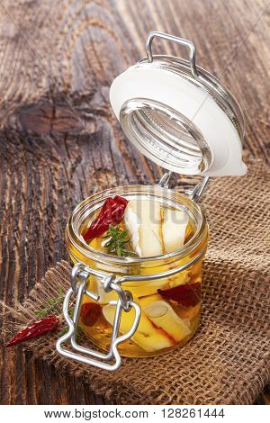 Marinated cheese in glass jar on brown wooden background. Culinary marinated cheese rustic styles.