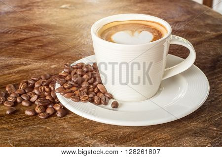 Heart-shaped pattern of coffee latte art with coffee beans valentine's day for background