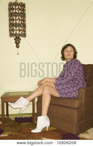 Pretty Caucasian mid-adult woman wearing vintage clothing sitting in brown retro chair looking bored.