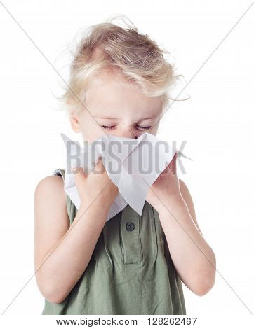 Little blond girl blowing her nose  on white background