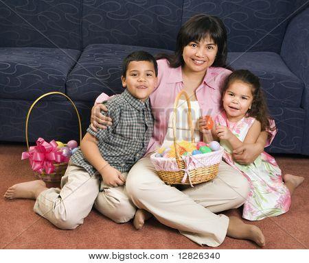 Família sentado no chão com cestas de Páscoa, sorrindo e olhando para o espectador.