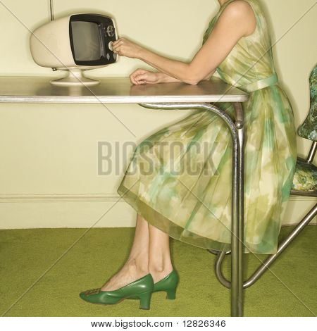 Side view of Caucasian mid-adult woman wearing green vintage dress sitting at 50's retro dinette set turning old televsion knob.