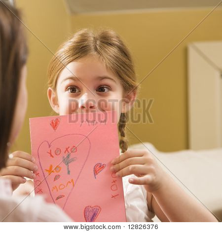 Niña caucásica dando a media madre adulta un dibujo.