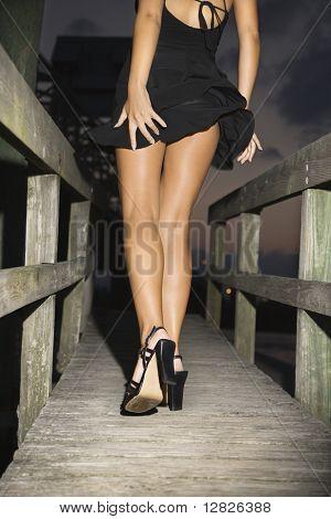 Back view of Caucasian mid-adult woman wearing little black dress and heels walking on wooden bridge.
