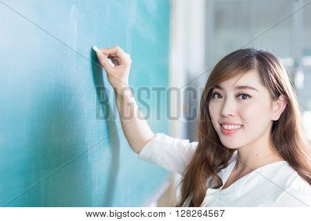 beautiful young girl with green blackboard in classroom