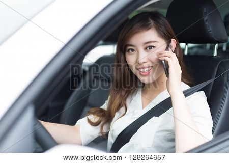 young beautiful asian girl with phone in car