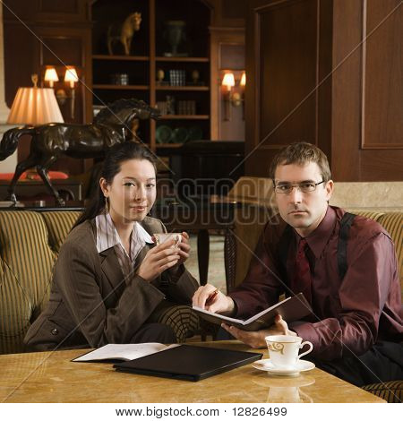 Caucasian mid adult businessman and woman drinking coffee and looking at viewer.