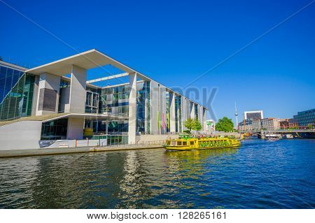 BERLIN, GERMANY - JUNE 06, 2015: Yellow, tropical islands, boat arrives to a modern construction on the river in Berlin, Marie Elisabeth Lueder house is one of parliamentan buildings