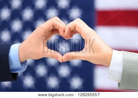 Two homosexuals making heart with their hands on American flag background