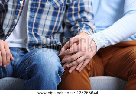 Two homosexuals sitting on sofa and holding each other hands