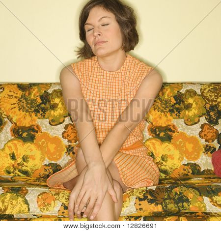 Pretty Caucasian mid-adult woman sitting on colorful retro sofa with arms crossed and eyes closed.