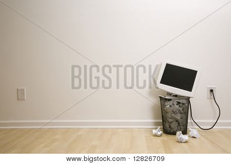 Computer monitor in trash can surrounded by crumpled up paper.