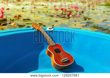 Ukulele lay on blue boat float on water lily lake