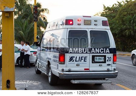 Ambulance Car At The Street Road With Blinking Lights. Helping People On Car Accident