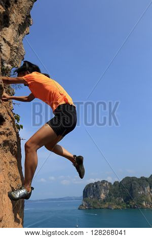 free solo woman rock climber climbing at seaside mountain rock wall