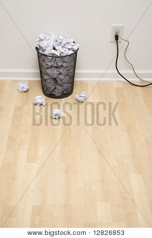 Full wire mesh trash can with crumpled paper next to electrical outlet and plugs.