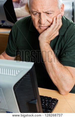 Senior Man With Hand On Chin Using Computer In Classroom