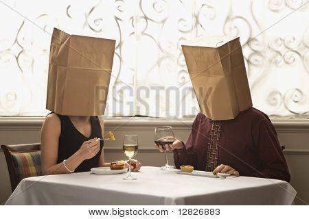 Mitte erwachsen europäisch-paar Restaurants in einem Restaurant mit Papiertüten über Köpfe hinweg.