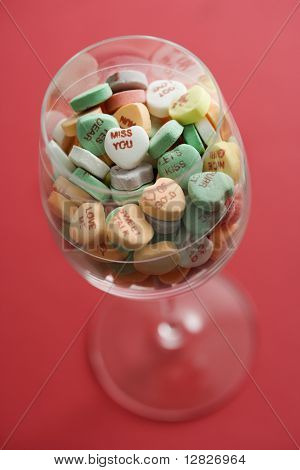 Wine glass full of colorful candy hearts with sayings on them on red background.
