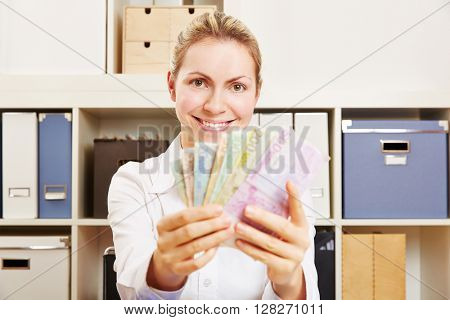Young smiling business woman with Euro money fan at her desk