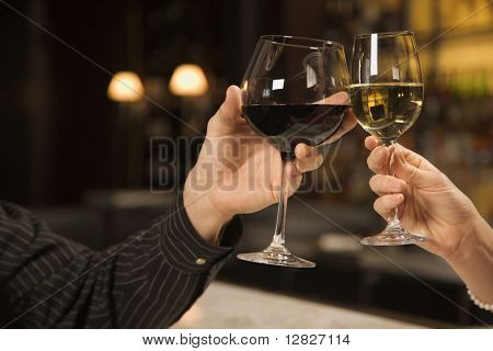 Mid adult Caucasian male and female hands toasting wine glasses.