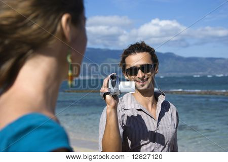 Mid-adult Caucasian man on beach pointing video camera at woman.