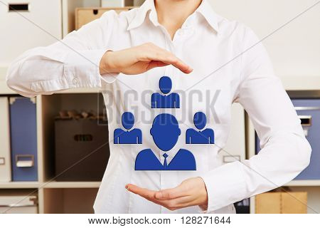 Hands of a business woman in office holding a network symbol with icons of people group