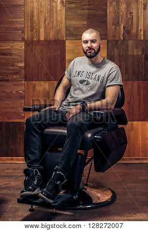 Happy client after beard haircut. Enjoying his perfect beard. Handsome young bearded man looking at the camera and sitting in a chair on a wooden texture.