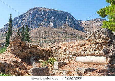 The ruins of an ancient Greek temple in Corinth at the foot of picturesque mountains. Peloponnese. Greece
