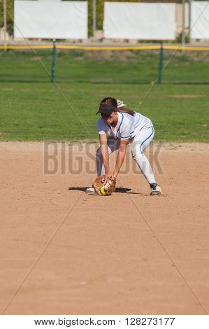 Female softball player playing defense on the infield.