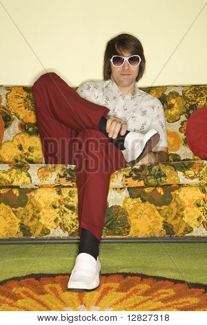 Caucasian mid-adult man sitting on colorful retro sofa wearing sunglasses looking bored.