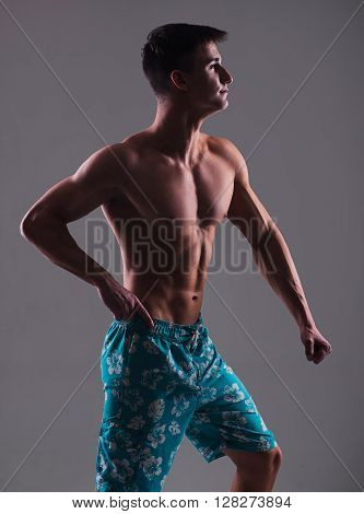 Young Muscular Bodybuilder Posing Over Gray Background. Men's Physique