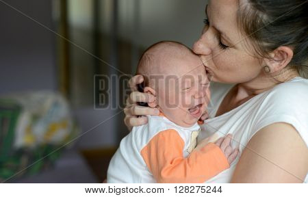 Close up of young mother holding her crying baby daughter, kissing her