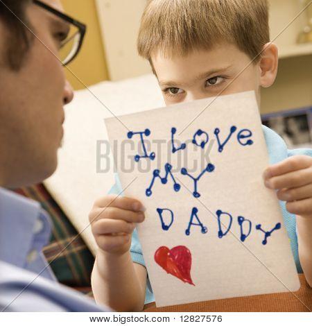 Niño caucásico dando a medio padre adulto un dibujo.