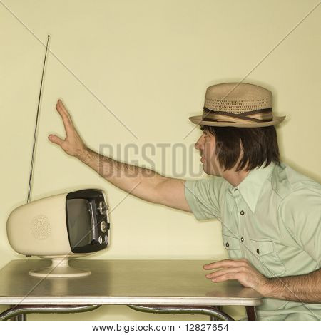 Side view of Caucasian mid-adult man wearing hat sitting at 50's retro dinette set adjusting old television antenna.