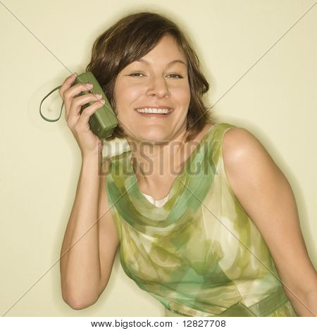 Pretty Caucasian mid-adult woman wearing green vintage dress holding handheld radio up to her ear and smiling at viewer.