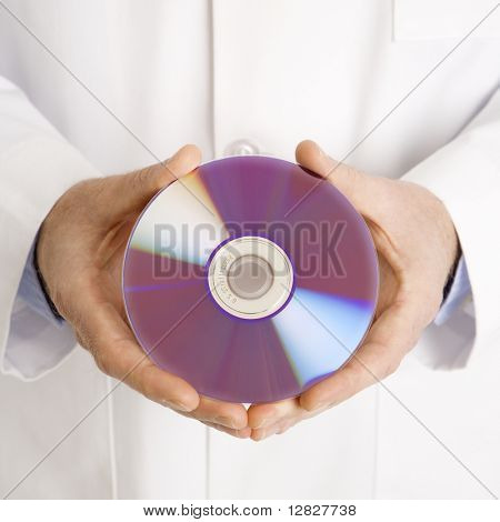 Close up of Caucasian mid adult male physician holding compact disc.