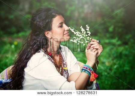 smiling young woman in boho style clothes hold lily of the valley side shot outdoor closeup