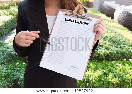 Women in suit showing Loan agreement and pointing with a pencil.